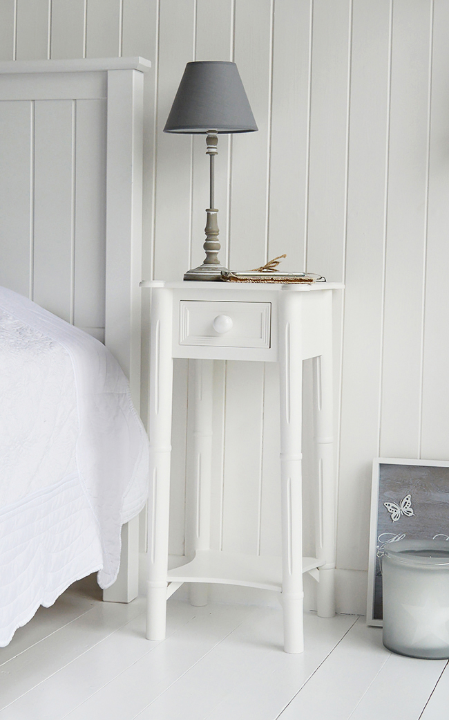 A Narrow Tall White Bedside Table With Drawer And Chunky