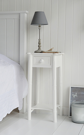 A narrow tall white bedside table with drawer and chunky knob handle The White Lighthouse