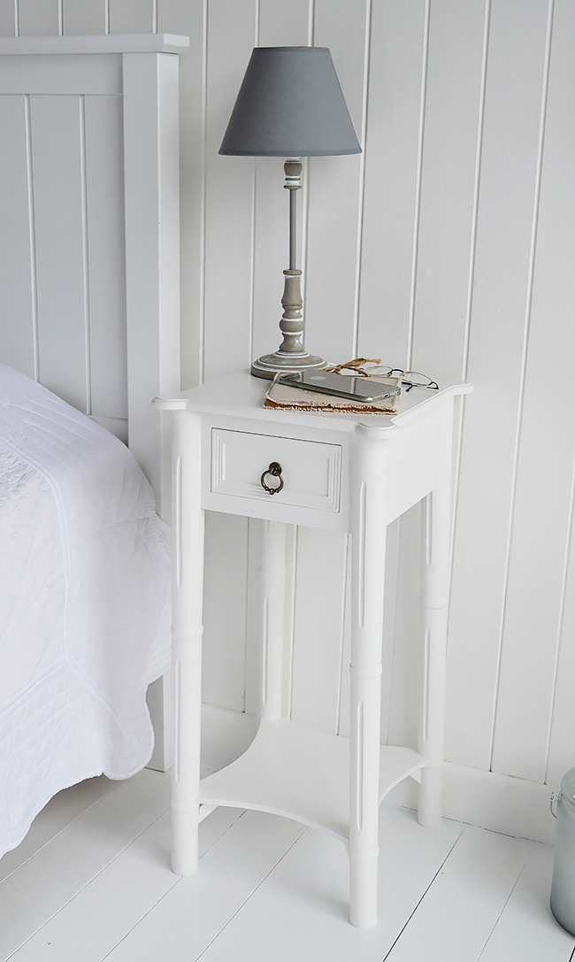 A narrow tall white bedside table with drawer New England