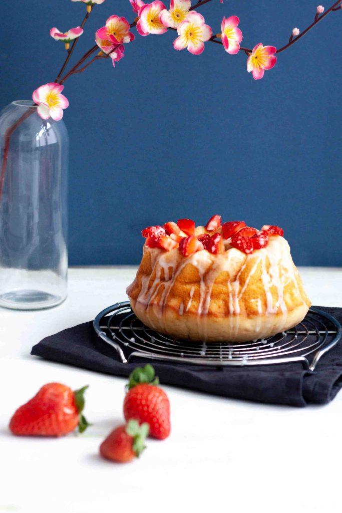 Ein Joghurtküchlein mit Zitronenglasur und Erdbeeren-Topping