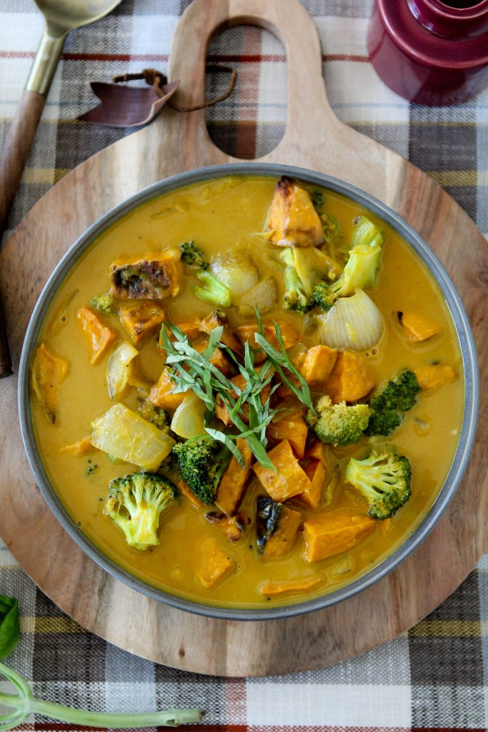 overhead shot of a bowl of vegan Pumpkin Curry garnished with chopped basil