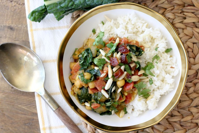 a bowl of vegan kale and chickpea curry served over white rice