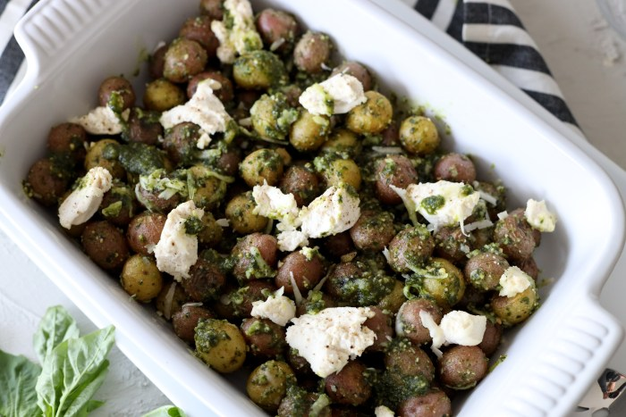 a white casserole dish with baby potatoes baked with pesto and topped with Italian cheeses