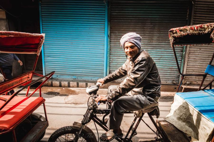 Chadni Chowk: a rickshaw driver smiles as he passes by