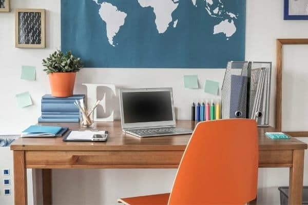 A styled office with world map background.