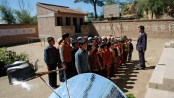 Gansu China. 2005 Children assemble in school courtyard. Solar panel disc heats kettle.