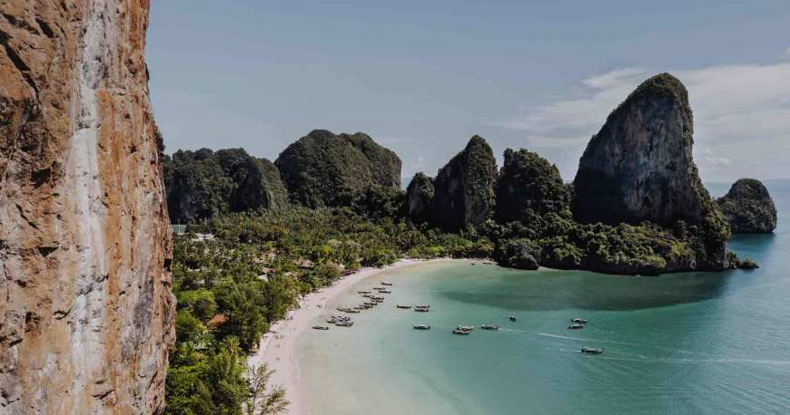A beach in Thailand surrounded by conic mountains
