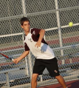 Michael, a junior, winds up to slam a cross- court shot.