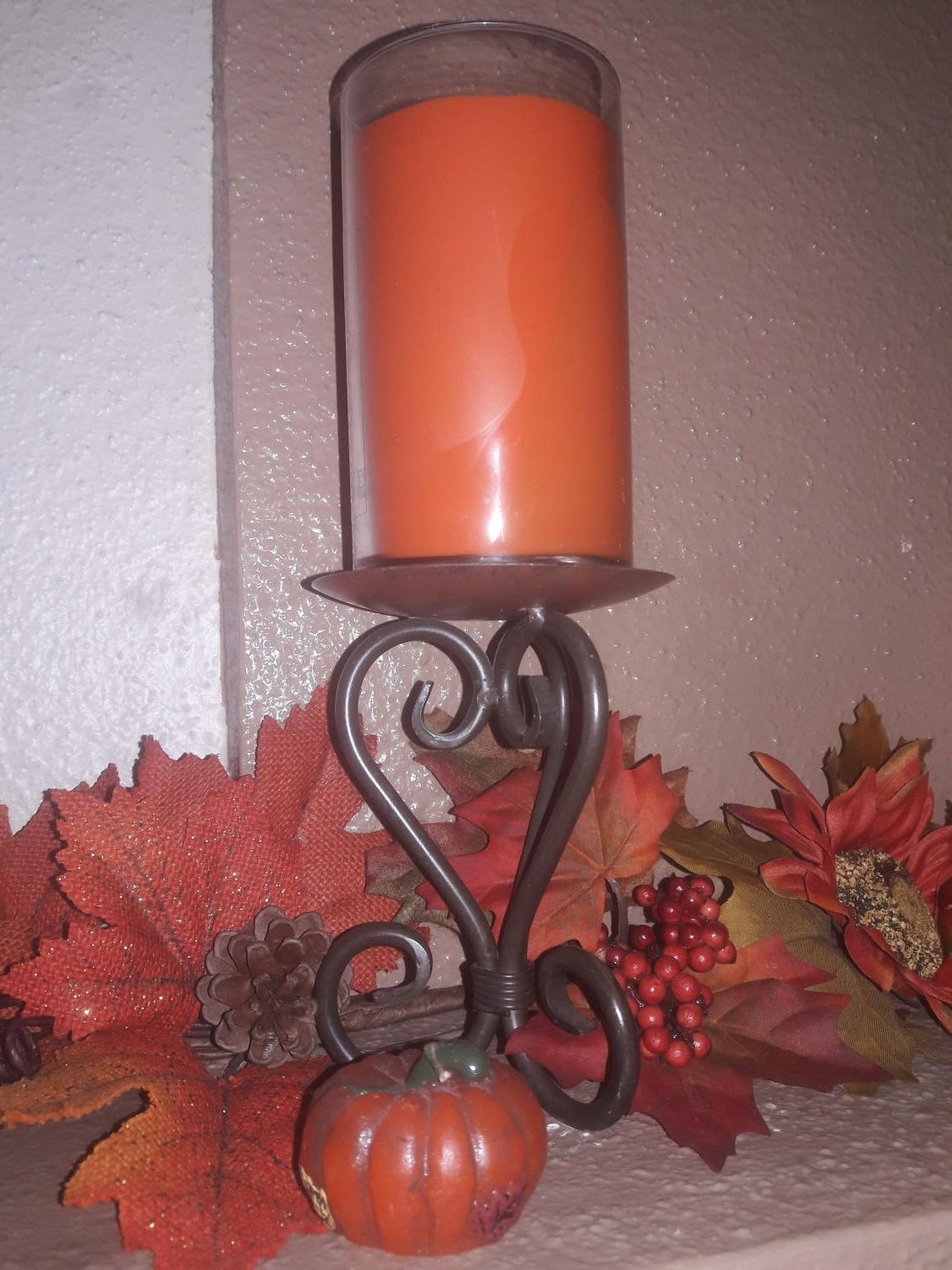 A Thanksgiving candle with fall leaves surrounding it.