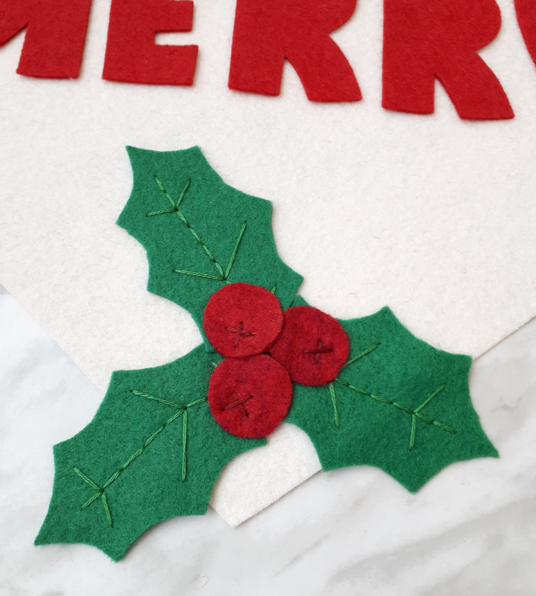 Hand sew the holly leaves and berries to give them more definition.