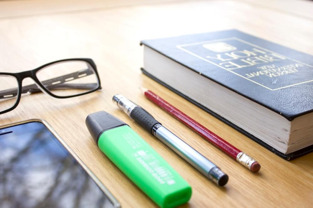 Image of book, stationary and glasses on a table
