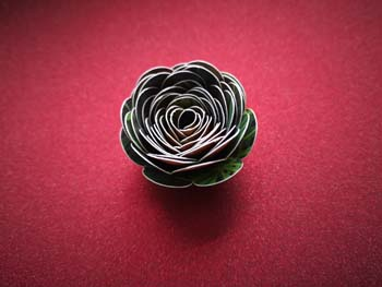 rolled paper flower on red glitter background