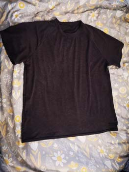 Grey T-shirt on a Grey floral duvet cover in the background
