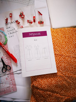 Flat Lay of Sewing Clips, Frixiion Pen, White Interfacing, Ruler, Scissors, Pattern Instructions, Pins And Marmalade Hearts Yellow Fabric