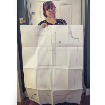 Picture of SaWhite Woman In Her 30's Holding A Copyshop Print Of Lucille Trouser Leg With A Confused Look On Her Face