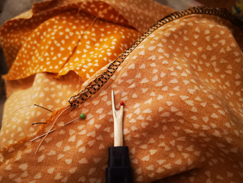 Seam ripper Unpicking Overloced Stitched Seams on Yellow Fabric