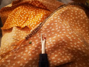 Seam ripper Unpicking Overloced Stitched Seams on Yellow Fabric