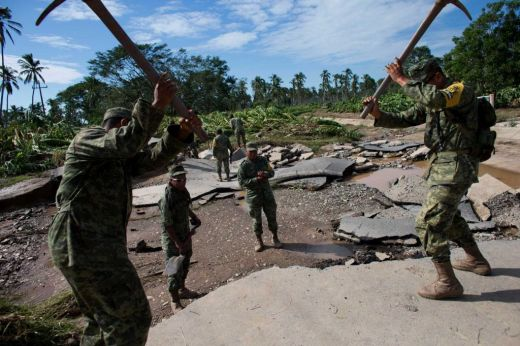 Soldiers break up a road washed away by floodwaters, to create a makeshift passage toward the village of Rebalse (timesunion.com)