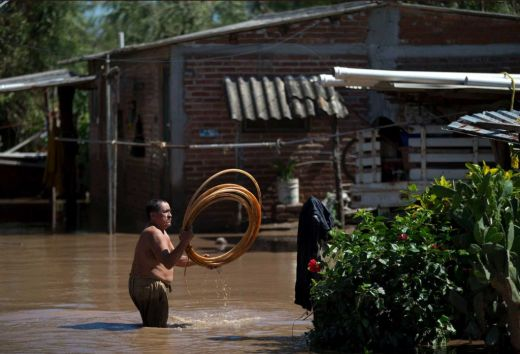 A man salvages items from his flooded front yard, two days after Hurricane Patricia, in the village of Rebalse (timesunion.com)