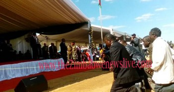 Chief Chirumhanzu, (partly obscurely in a shiny suit) together with other members of the local traditional leadership kneel down to greet President Mugabe