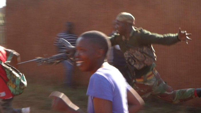 Savage ... A soldier lunges at a man with a bayonet in Harare on August 1. Seven people were killed in the brutal attacks on civilians (Picture SABC)