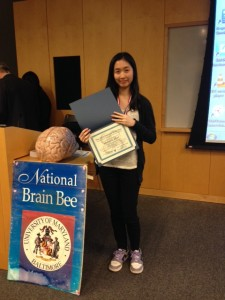 Hetince stands with her certificate after competing at the National Brain Bee at the University of Maryland.