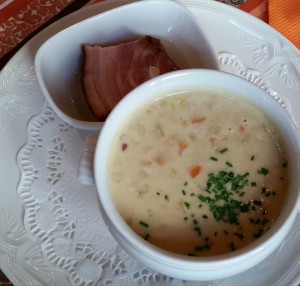 Creamy barley soup with diced veggies and speck