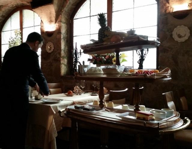 waiter preparing dessert from the dessert trolley