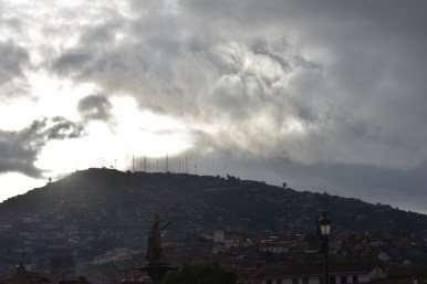 The sun breaks through clouds over a statue of the Inca.