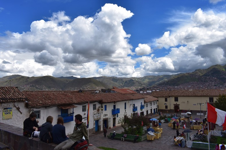 Some travelers sit at the Plaza San Blas.