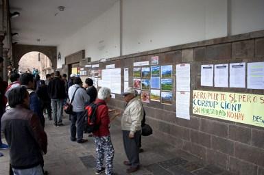 Protestors put up fliers near the Plaza de Armas.