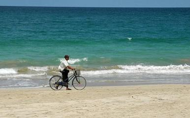 man with bicycle on the beach in Ngapali