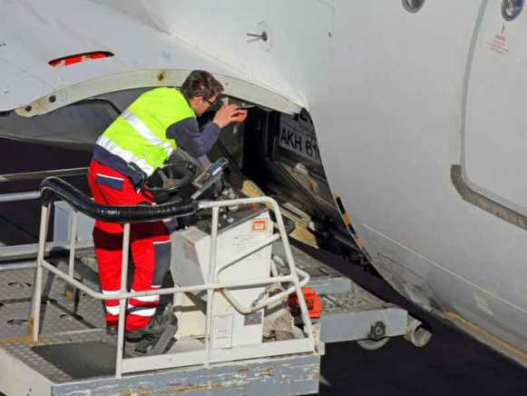 Airplane technician servicing a cargo hatch on a jet.