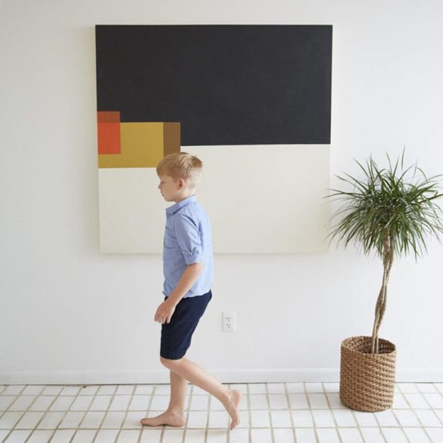 Tips for displaying art: A young boy walks by a palm and a piece of modern art
