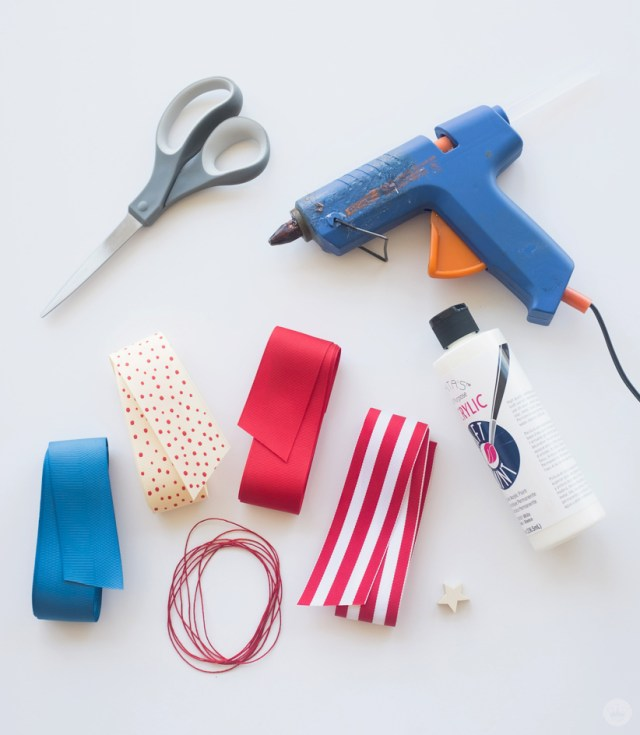 Fourth of July Ribbon Garland supplies: scissors, glue gun, ribbon, cord, fabric paint, stamp.