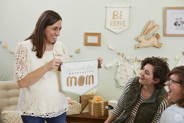"""Baby shower guests with """"reserved for Mom"""" sign"""