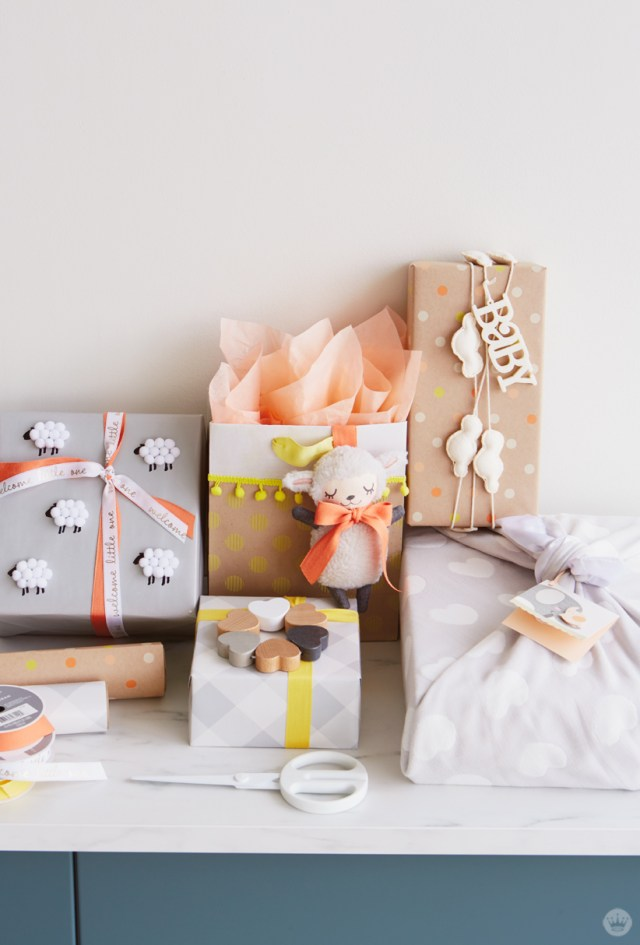 Baby gift wrap ideas using products from Hallmark, clockwise from top right: Gift wrapped in a cloud garland, box wrapped in a heart-covered blanket, gray gingham box with wooden rattle, gray wrap with pom-pom sheep, gift bag with pom-poms and attached plush lamb toy.