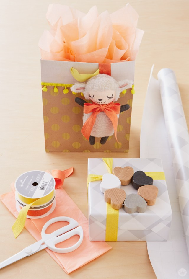 Polkadot and pom-pom gift bag with orange tissue and plush lamb attachment. Also shown: Gray gingham-wrapped box with yellow ribbon and wood rattle, plus scissors and gift wrap supplies