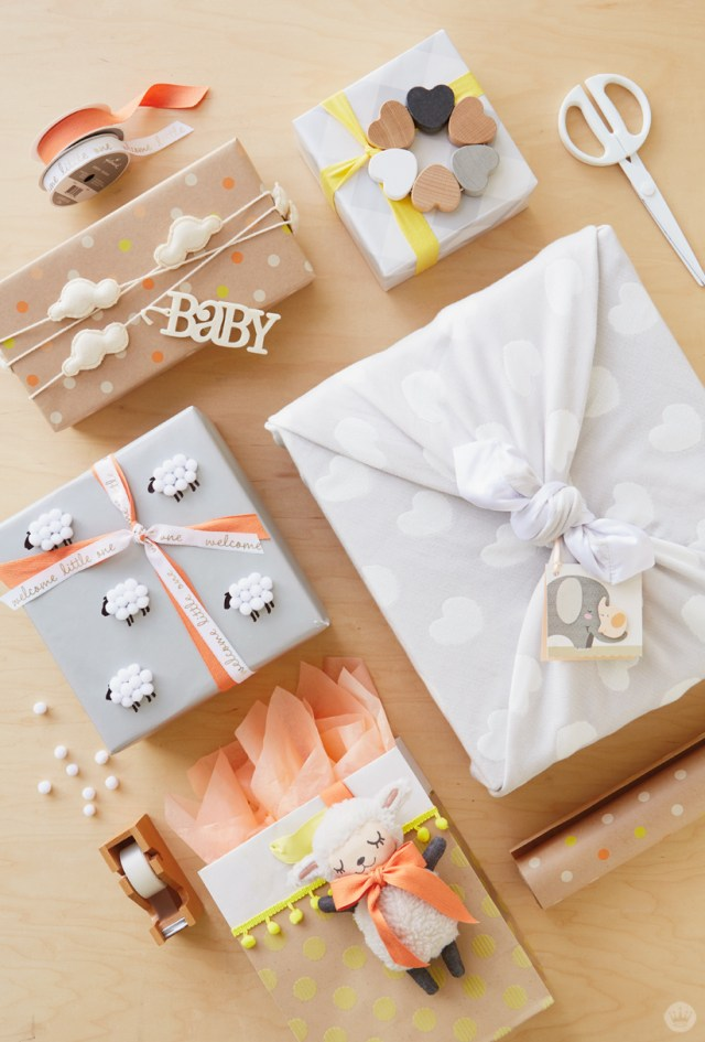 Five baby gift wrap ideas, clockwise from top right: Tie a rattle to the top, tie a heart-covered blanket around a box, add a lamb to a bag, add a flock of fuzzy sheep, use a garland as ribbon.