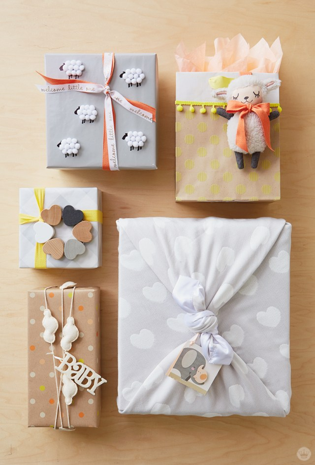 Five baby gift wrap ideas, clockwise from top right: Add a lamb to a bag, tie a heart-covered blanket around a box, use a garland as ribbon, tie a rattle to the top, and add a flock of fuzzy sheep.