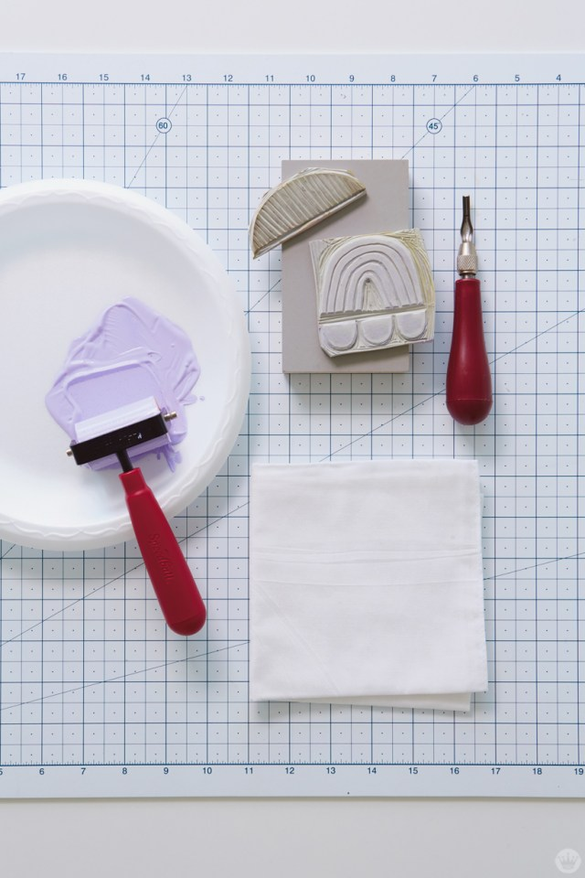 Tools for block print gifts: brayer, linoleum block, rubber stamp carving tool, fabric paint, plain white bandana, cutting board