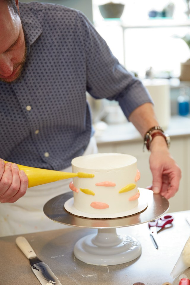 "Using a piping bag to apply ""worms""—squiggly lines of buttercream—to a white, pre-iced cake"