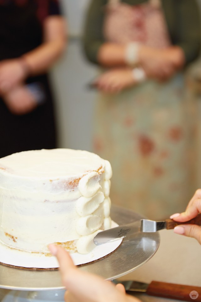"Using an offset spatula to flatten dots of buttercream frosting on a layered ""petal cake"""
