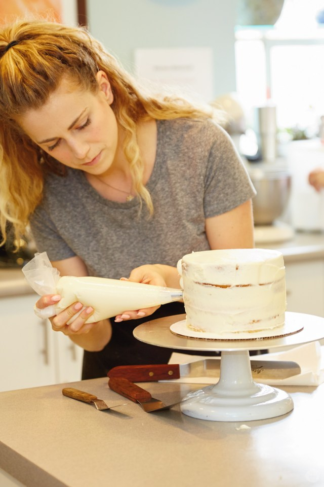 Using a piping bag to apply frosting to a layer cake