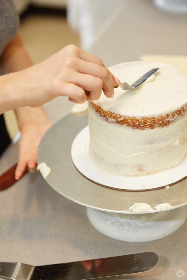 Using an offset spatula to apply buttercream frosting to the top of a layer cake