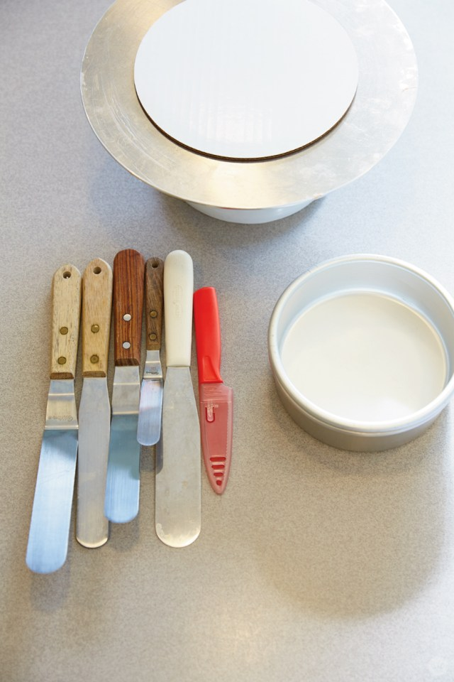 Cake Decorating supplies: rotating stand, cardboard cake boards, offset spatulas, knife, cake pans