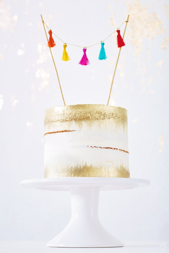 DIY cake toppers: Naked cake with gold accents decorated with tassel garland topper