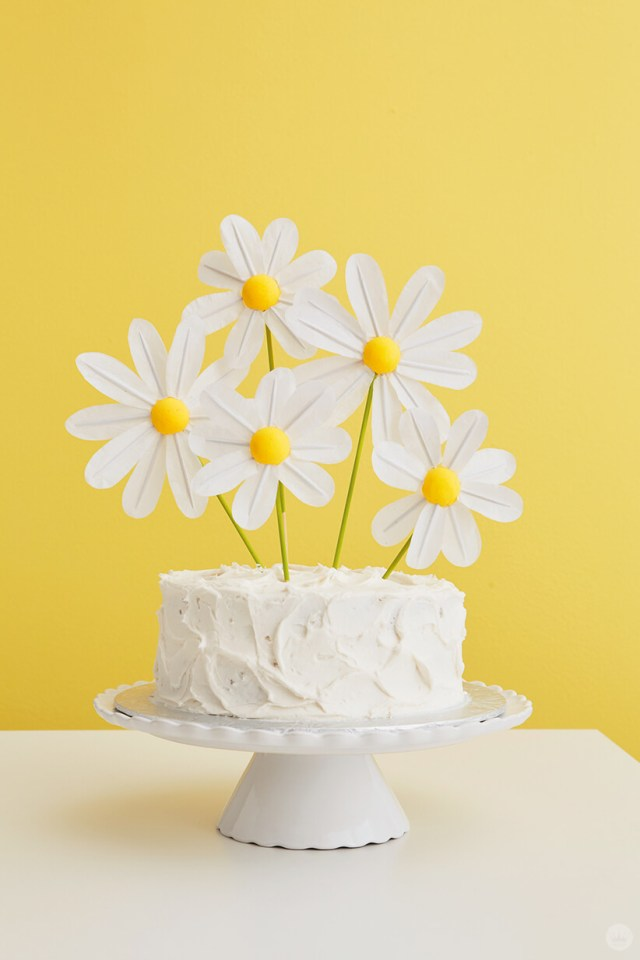 DIY Daisy Cake Toppers on a white frosted cake