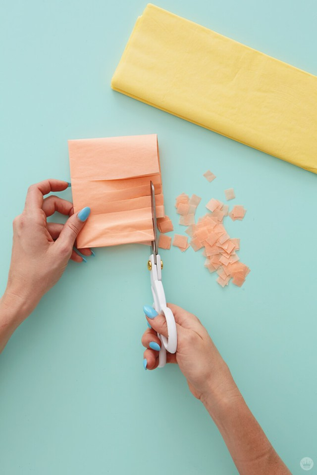 Cutting squares from tissue paper to make confetti | thinkmakeshareblog.com