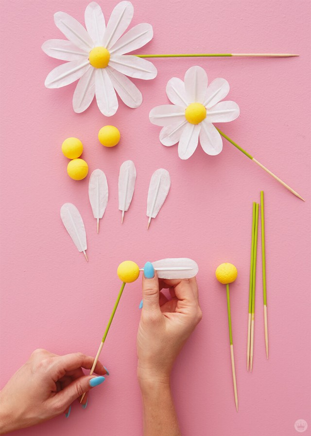 Adding tissue paper petals to DIY Daisy Cake Toppers